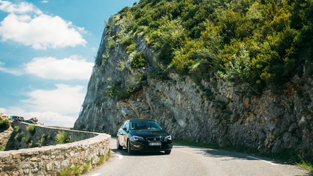 Black colour Seat Leon 5-door car on background of French mountain