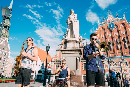Riga Latvia Street Music Trio Band, Three Young Guys Playing Instruments For Donation On The Town Hall Square