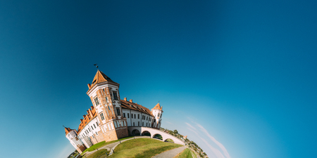 Mir, Belarus. View Of Old Towers Of Mir Castle Complex On Blue Sunny Sky Background. UNESCO Heritage. Famous Landmark In Summer In Funny Panorama Like Half Part Of Little Planet Stock Photo