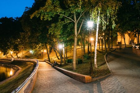 Gomel, Homiel, Belarus. Lighted Walkways Or Roads, Greenwood At Blue Hour Of Evening Or Night In City Park. Popular Place For Tourists And Locals In Gomel, Belarus. Stock Photo