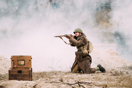 Re-enactor Dressed As Red Army Russian Soldier Of WWII Aiming With Rifle On Battlefield.