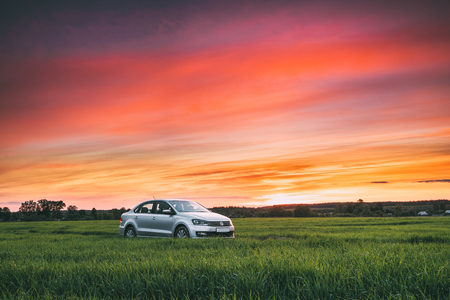 sedan: Volkswagen Polo Vento Car Sedan On Country Road In Spring Wheat Editorial