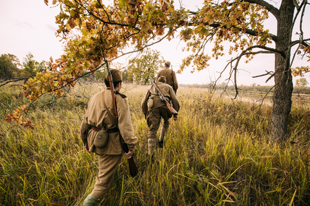reenactment: Group Of Reenactors Men Dressed As Russian Soviet Red Army Infantry Soldiers Of World War II Marching In Autumn