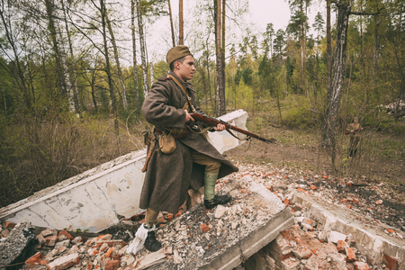 Re-enactor Dressed As Soviet Russian Red Army Infantry Soldier Of World War II Is Performing Mopping-up Operation With Rifle Along Rubble Building
