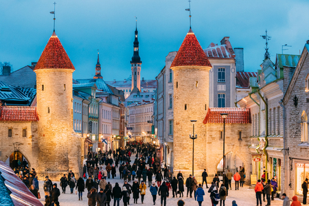 Tallinn, Estonia - December 3, 2016: People Walking Near Famous Landmark Viru Gate In Street Lighting At Evening Or Night Illumination. Christmas, Xmas, New Year Holiday Vacation In Old Town. Popular Touristic Place