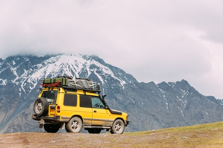 Yellow SUV Car On Off Road In Spring Mountains Landscape In Georgia. Drive And Travel Concept. Landscape Of Gorge At Spring Season. Stock Photo