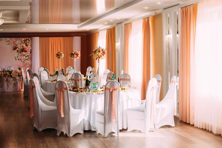 Dekorative weiße Umhänge und farbigen Bänder auf Stühle am Festlicher Tisch