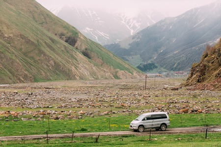 Mitsubishi Delica Space Gear on off road in Georgian summer mountains landscape.