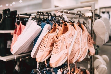 consumerism: Close View Of Fashion Casual Female Sneakers On Hunger In Store Stock Photo
