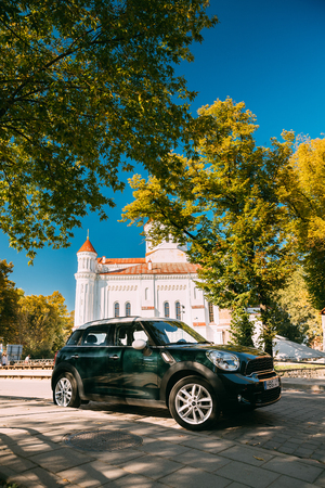 Vilnius, Lithuania. Green Color Mini Cooper Car Parking Near Cathedral Of Theotokos In Vilnius