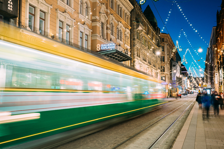 Helsinki, Finland - December 6, 2016: Tram Departs In Motion Blur From Stop On Aleksanterinkatu Street In Kluuvi District In Evening Night Christmas Xmas New Year Festive Illumination.