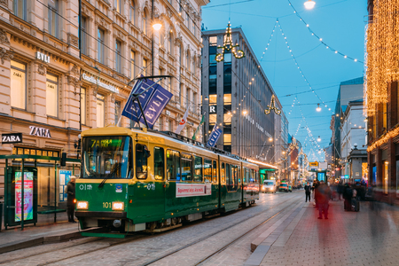 Helsinki, Finland - December 8, 2016: Tram Departs From A Stop On Aleksanterinkatu Street. Night View Of Aleksanterinkatu Street In Kluuvi District In Evening Or Night Illumination. Editorial