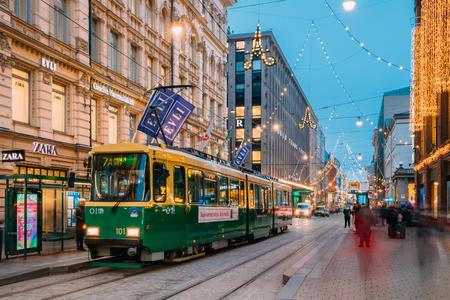 Helsinki, Finland - December 8, 2016: Tram Departs From A Stop On Aleksanterinkatu Street. Night View Of Aleksanterinkatu Street In Kluuvi District In Evening Or Night Illumination. Editoriali