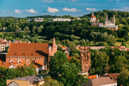 Vilnius, Lithuania. View Of Church Of St. Anne, Church of St. Francis and St. Bernard, Church Of Ascension And Church Of Sacred Heart Of Jesus Among Green Foliage