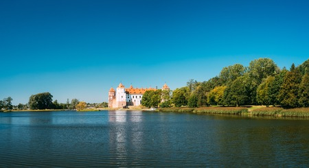 Mir, Belarus. Panoramic View Of Mir Castle Complex From Side Of Lake. Architectural Ensemble Of Feudalism, Ancient Cultural Monument, Famous Landmark In Summer Sunny Day Under Blue Sky, Copyspace. Stock Photo
