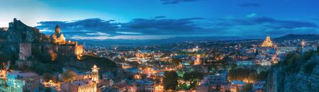 Tbilisi, Georgia. Panorama Of Narikala Fortress, Bridge Of Peace, Music Hall, Metekhi Church, Presidential Administration Palace, Sameba Holy Trinity Cathedral In Evening Night Illumination Stock Photo