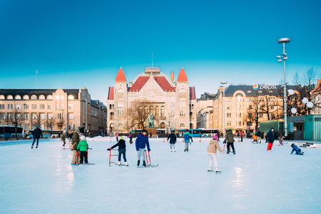 Helsinki, Finland. Children Skating On Rink On Railway Square On Background Of Finnish National Theatre In Winter