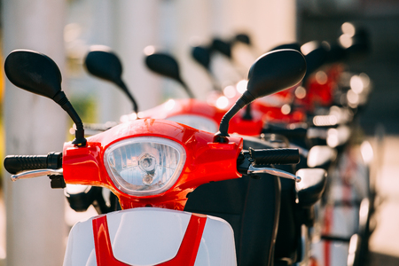 Many Electric Motorbikes, Motorcycles Scooters Parked In Row In City