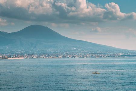 Naples, Italy. Man Training On Kayak In Tyrrhenian Sea. Landscape With Volcano Mount Vesuvius And Tyrrhenian Sea In Sunny Summer Day
