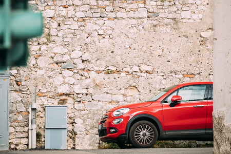 Terracina, Italy. Red Color Fiat 500X Car Parked On Background Old Wall.