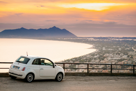 Terracina, Italy. White Color Fiat 500 Facelift 2016 Car Parked On Background Circeo Promontory And Tyrrhenian Sea In Sunset Or Sunrise Time Redakční