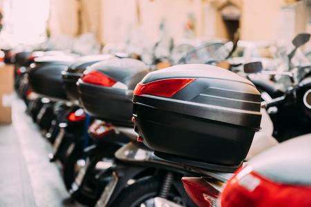 Roller mit abnehmbarem Kofferraum. Viele Motorräder, Motorräder, Motorroller in Reihe in der City Street geparkt. Close Up Kofferraum oder Top-Box ist ein Staufach hinter dem Sitz