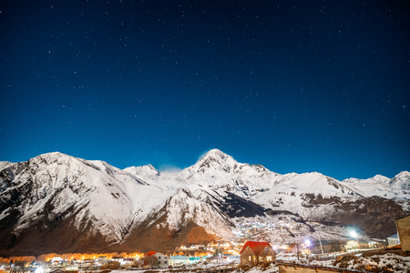 Stepantsminda, Georgia. Winter Night Starry Sky With Glowing Stars And Aircraft Light Trail Over Peak Of Mount Kazbek Covered With Snow. Beautiful Night Georgian Winter Landscape Stock Photo