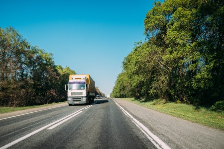 Truck In Motion On Country Road. Tractor Unit, Prime Mover, Traction Unit In Motion On Countryside Road In Europe. Business Transportation And Trucking Industry Concept Foto de archivo