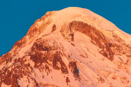 Georgia. Mount Kazbek Covered Snow In Winter Sunrise. Morning Dawn Colored Top Of Mountain In Pink-orange Colors. Awesome Winter Georgian Nature Landscape. Banco de Imagens