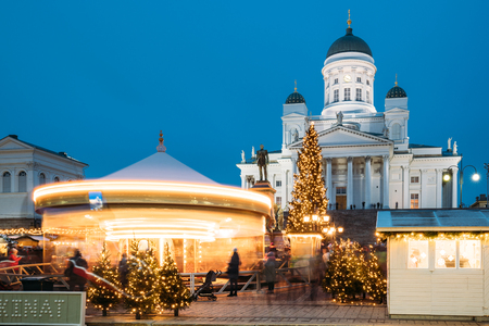 Helsinki, Finland. Xmas Market On Senate Square With Holiday Carousel And Famous Landmark Is Lutheran Cathedral And Monument To Russian Emperor Alexander II At Winter Evening Stock Photo - 124126207