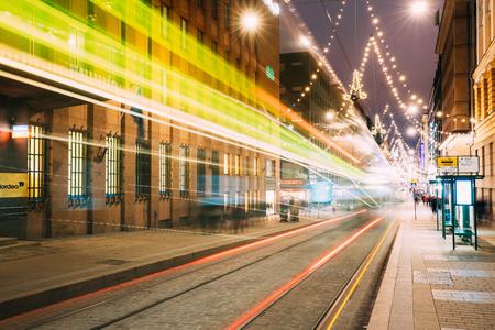 Helsinki, Finland. Tram Departs In Motion Blur From Stop On Aleksanterinkatu Street In Kluuvi District In Evening Night Christmas Xmas New Year Festive Illumination Editorial