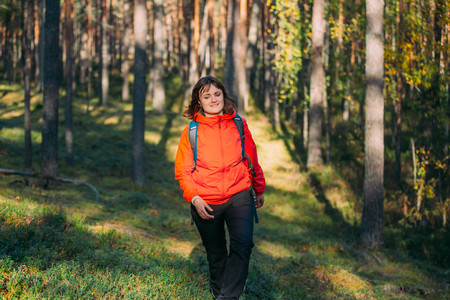 Active Young Beautiful CaucasianLady  Woman Dressed In Red Jacket Walking In Autumn Forest. Active Lifestyle In Fall Age Nature