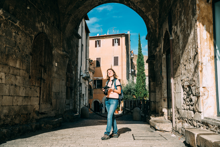 Terracina, Italy. Young Caucasian Woman Taking Photos In Gothic Palazzo Venditti