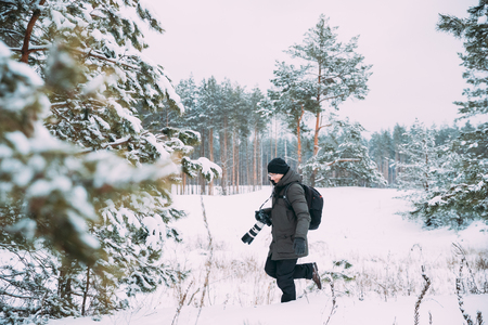 Young Man Backpacker With Photo Camera Taking Photo In Winter Snowy Forest. Active Hobby. Hiker Walking In Snowy Pinewood Forest