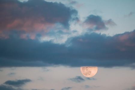 Full Moon Rising In Cloudy Evening Sky