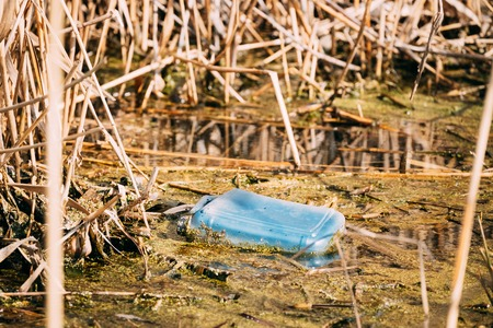Old Plastic Canister Floats In Water Of Swamp Or Pond. Used Empty Packing Materials Left In Water. Eco Concept Garbage Disaster From Ecological Pollution Of Environment. Waste Pollution Problem