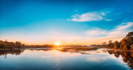 Autumn River Landscape In Belarus Or European Part Of Russia At Sunset. Sun Shine Over Blue Water Lake Or River At Sunrise. Nature At Sunny Morning. Woods With Orange Foliage On Riverside