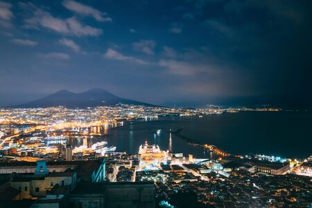 Naples, Italy. Top View Cityscape Skyline Of Naples With Mount Vesuvius And Gulf Of Naples In Background In Evening Or Night Illuminations