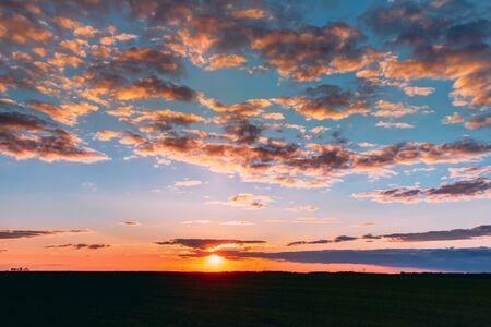 Natürlicher Sonnenuntergang Sonnenaufgang über Feldwiese. Heller dramatischer Himmel und dunkler Boden. Landschaft unter malerischen bunten Himmel bei Sonnenuntergang Sonnenaufgang Sonnenaufgang. Skyline, Horizont. Warme Farben. Standard-Bild