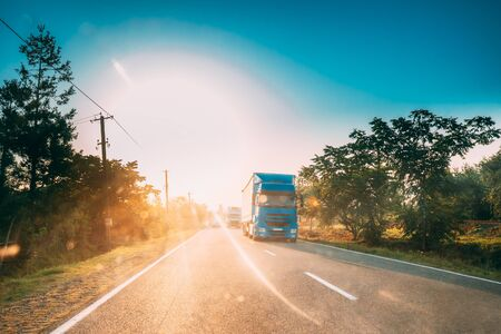 Truck In Motion On Country Road In Sunset Sun Sunshine Natural Sunlight. Tractor Unit, Prime Mover, Traction Unit On Countryside Road In Europe. Business Transportation And Trucking Industry Concept