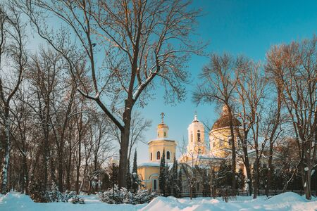 Gomel, Belarus. Winter City Park. Peter And Paul Cathedral In Sunny Winter Day. Famous Local Landmark In Snow.