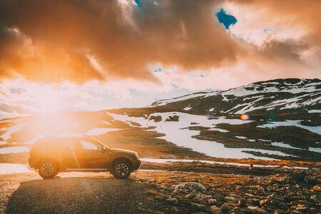 Aurlandsfjellet, Norway. Car SUV Parked Near Aurlandsfjellet Scenic Route Road In Summer Norwegian Landscape. Popular Destination In Sunset Lights.