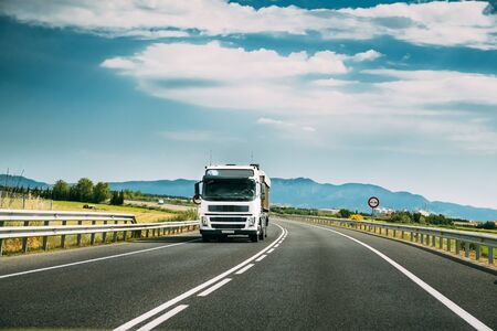 White Truck Or Traction Unit In Motion On Road, Freeway. Asphalt Motorway Highway Against Background Of Mountains Landscape. Business Transportation And Trucking Industry.