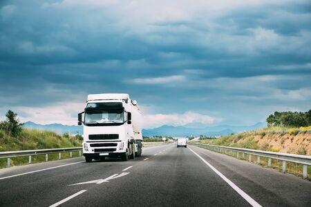 Weißer LKW oder Zugmaschine in Bewegung auf der Straße, Autobahn. Asphalt-Autobahn-Autobahn vor dem Hintergrund der Gebirgslandschaft. Business Transport- und LKW-Industrie.