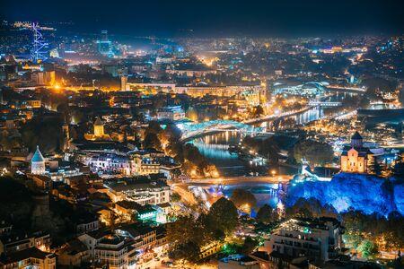 Tbilisi, Georgia. Top View Of Georgian Capital City Skyline Cityscape In Night Illuminations.