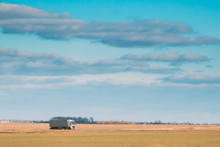 Truck Or Tractor Unit, Prime Mover, Traction Unit In Motion On Road, Freeway. Asphalt Motorway Highway Against Background Of Spring Meadow Field Landscape. Business Transportation And Trucking Industry