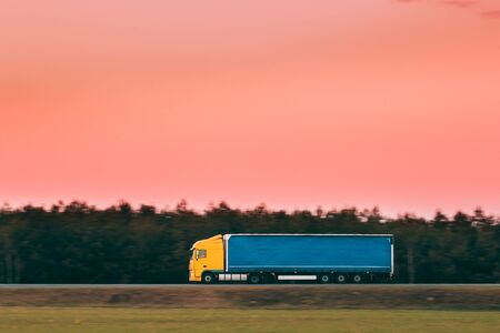 Yellow Truck Or Tractor Unit, Prime Mover, Traction Unit In Motion On Road, Freeway. Asphalt Motorway Highway Against Background Of Forest Landscape. Business Transportation And Trucking Industry
