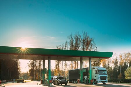 Car And Truck Tractor Unit, Prime Mover, Refuel At Gas And Oil Station In Sunny Autumn Day.