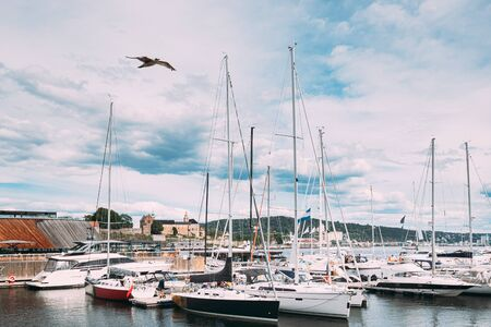 Oslo, Norway. Moored Boats And Yachts At Aker Brygge District. Seascape Of Harbour And Quays In Summer Day Under Scenic Cloudy Sky.