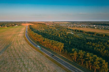 Aerial View Of Highway Road Through Field And Summer Green Forest Landscape. Top View Of Truck Tractor Unit Prime Mover Traction Unit In Motion On Freeway. Business Transportation, Trucking Industry.
